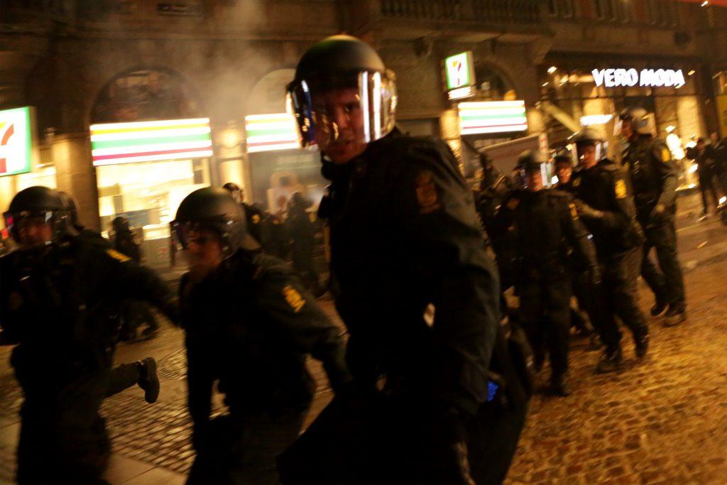 Politibetjenten ses her et sekund inden skubbet mod Redox-fotografen. Foto: Redox.