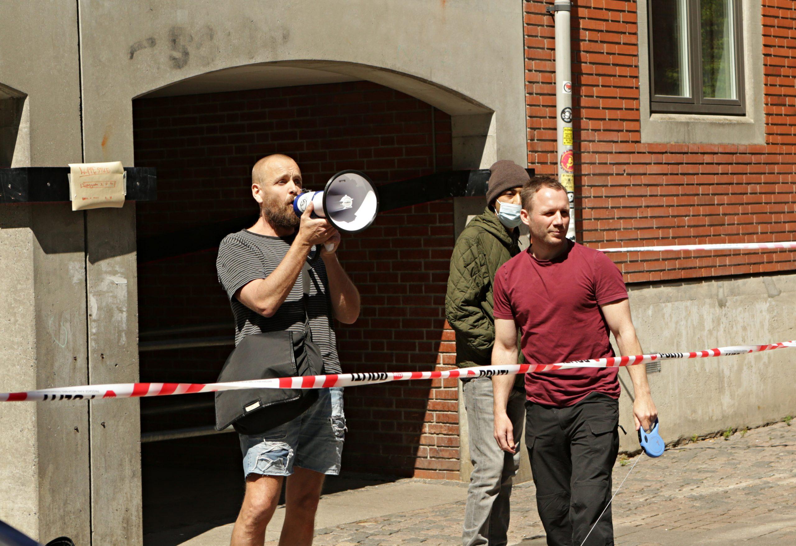 Lars Theilade (med megafon) taler under Patrioterne Går Lives demonstration på Nørrebro søndag. I rød tshirt ses Toke Lorenzen. Foto: Redox